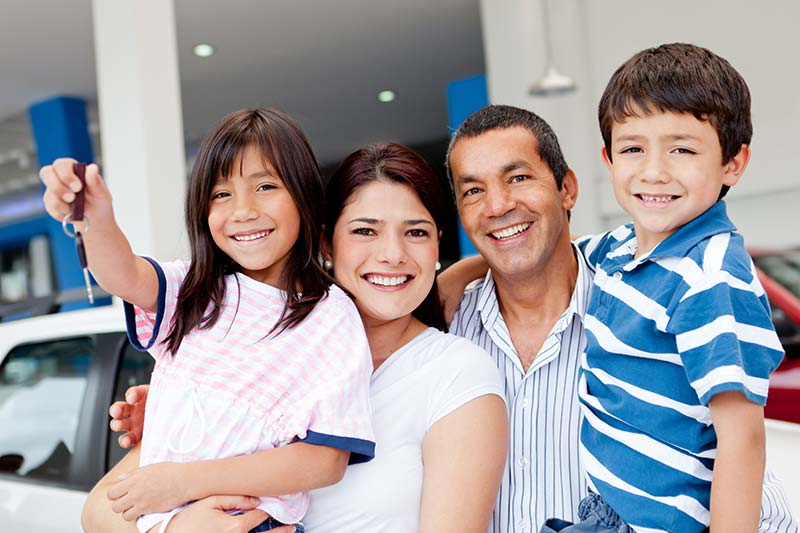 Happy Family With Daughter Holding A Set Of Keys