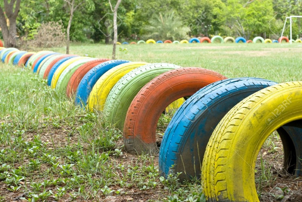 14373930-old-tires-with-colorful-paint-on-a-playground-Stock-Photo