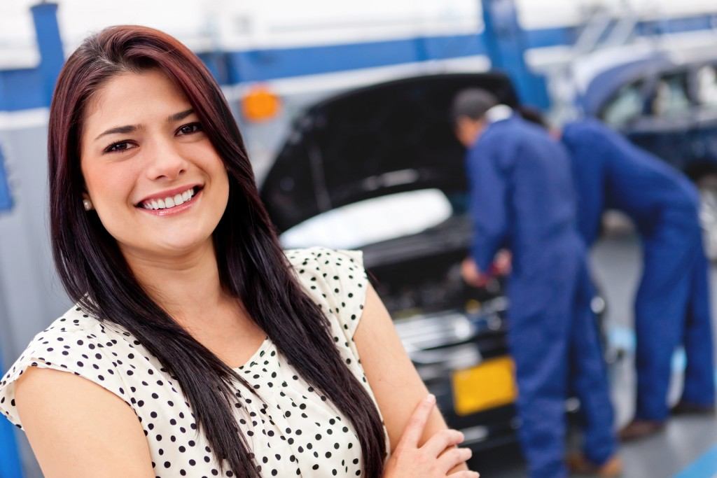 Woman at a car garage getting mechanical service