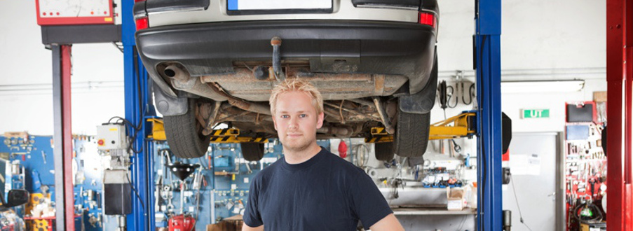 mechanic standing in front of auto in shop