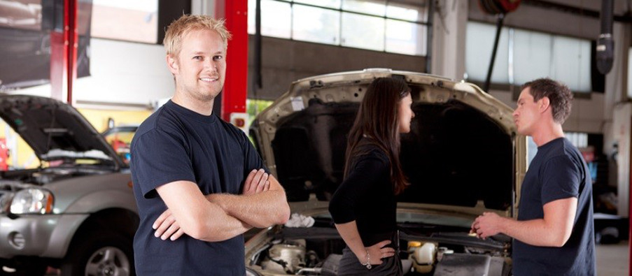 Mechanic looking at camera with customer and second mechanic in background