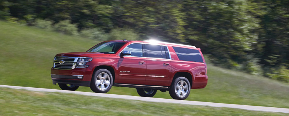 Red Suburban cruising up a hill
