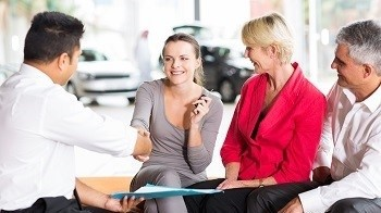 car salesman handshaking with young buyer